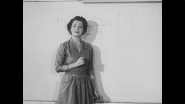 1950s: Students sit at desks in classroom, look at books, write, talk. Teacher stands at whiteboard, writes. Girl raises hand, talks.
