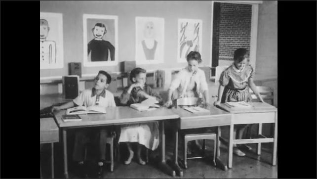 1950s: Writing on a whiteboard. Kids rearrange desks and tables into a line. Teacher stands in front of students, talks.
