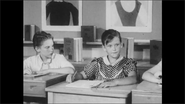 1950s: Girl sits at desk in classroom, talks. Students sit at desks, listen. Woman talks.