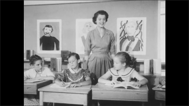 1950s: Girls sit at desks, one girl talks. Teacher walks behind girls, talks.