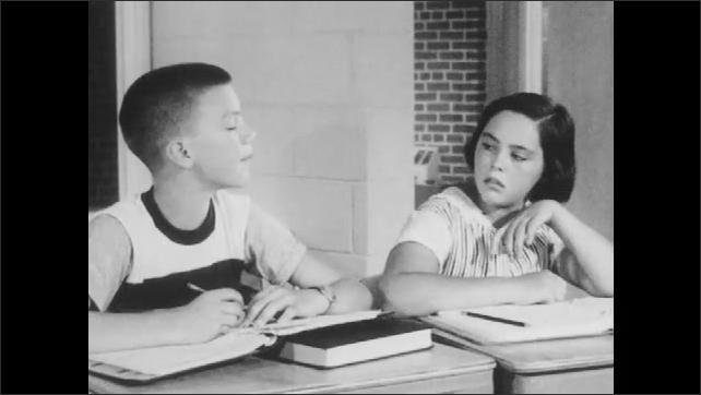 1950s: Boy sits at desk, talks. Boy sits next to girls, talks.