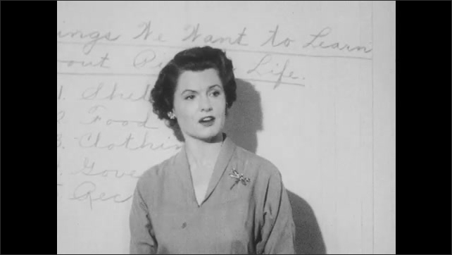 1950s: Woman stand in front of whiteboard, talks. Students sit at desks, boy talks, other kids laugh.