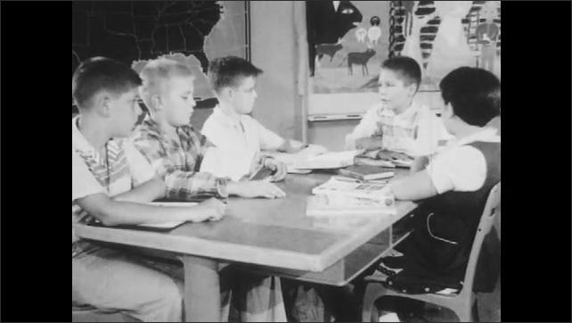 1950s: Students sit around table, talk.