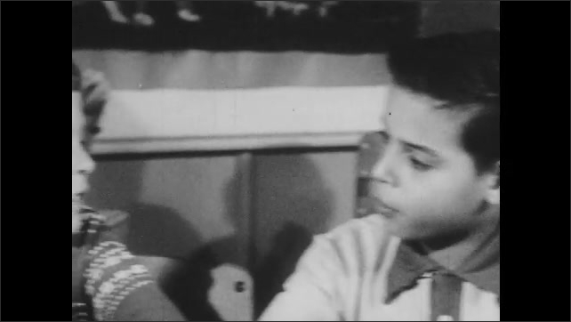 1950s: Boy points to picture of a house in a book. Two boys have a conversation. Boy turns around, talks to teacher.
