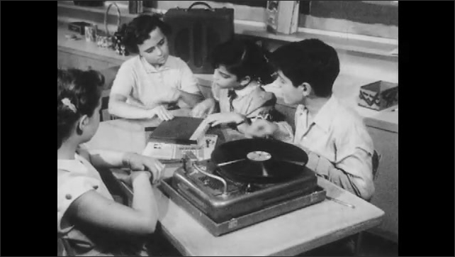 1950s: Students sit at table, listen to record. Boy takes needle off record. Students talk, look at book.
