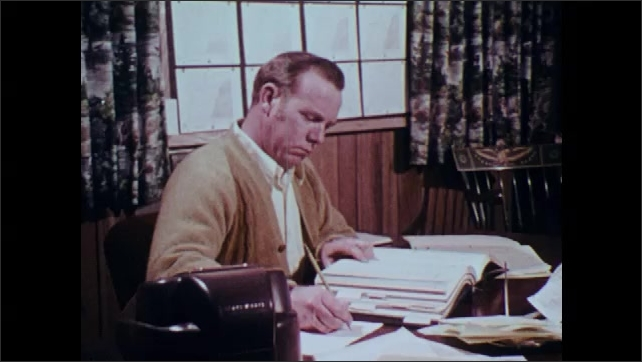 1970s: Office.  Man sits at desk and works.
