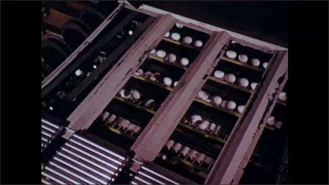 1970s: Machine sorts eggs.  Eggs move down conveyor belt.