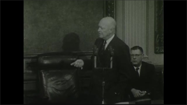 1950s: UNITED STATES: view towards journalists and president in room at press conference. Close up of president speaking. Journalist stands and sits. Journalist asks question