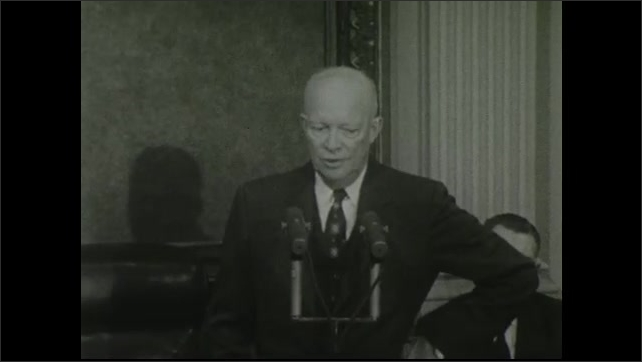 1950s: Zoom in on Dwight Eisenhower speaking at microphones.