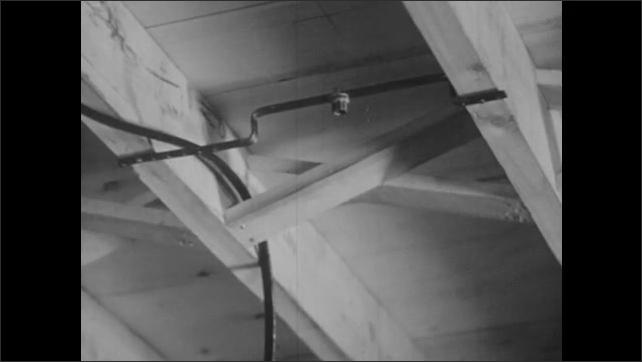 1940s: Hands hammer metal bar onto ceiling. Tilt down, man climbs down from ladder, picks up blueprint.