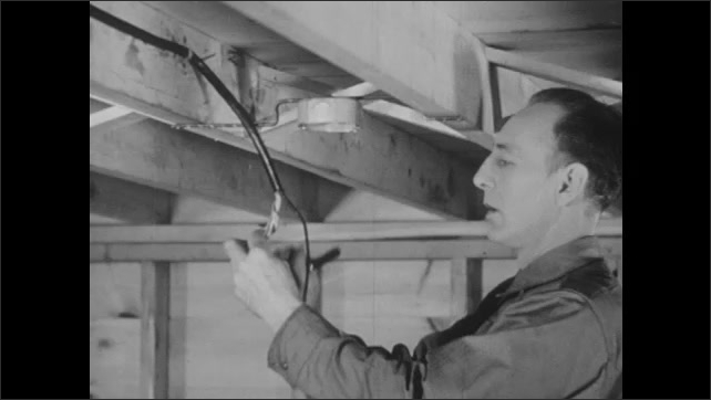 1940s: Man in frame of house, removes covering from electrical cable.