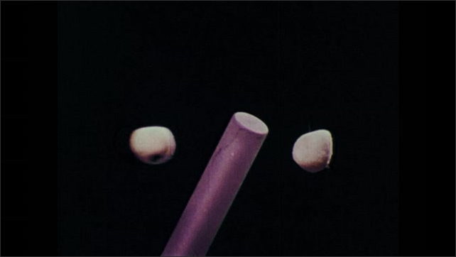 1970s: Two balls dangle from strings. Rod goes between the ball and all move the same distance away from the rod.