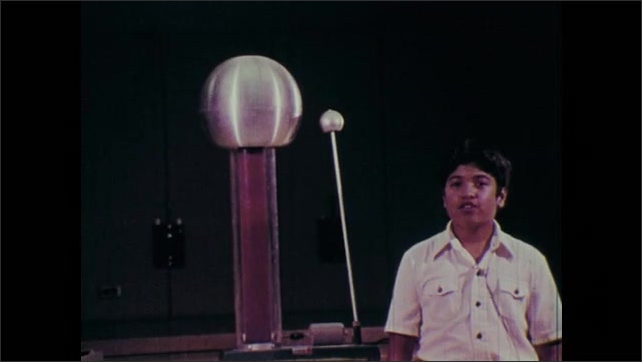 1970s: Static electricity generator sparks. Boy explains and shows the generator.