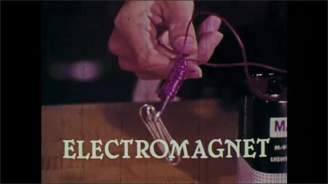 1970s: An electromagnet is created from a battery and wire. The electromagnet picks up paper-clips. Wire is removed from one battery post.