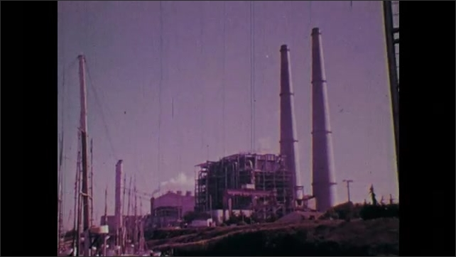 1970s: Steam powered electrical station. Electrical towers and lines at sunset.