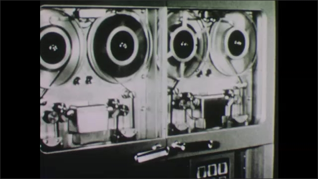 1960s: A woman presses a button on a computer. A man walks along a wall of data processors. Data tapes on machine. Man pulls out drawer and examines the guts of the machine.
