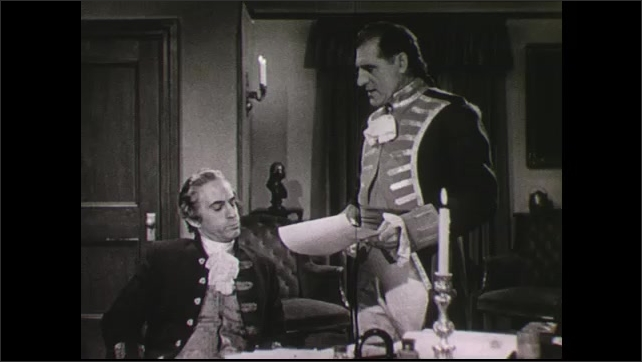 1940s: Revolutionary era military man stands in candlelit study, speaks to seated war secretary about sheet of paper.