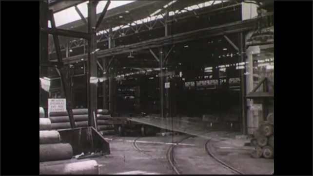 1940s: Man holds yarn, sits on bench as woman wraps yarn, smiles. Industrial manufacturing cable car travels across track. Dark factory assembly line. City skyscrapers along water, boats travels by.