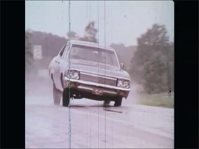 1970s: UNITED STATES: car swerves on road. Car overtakes vehicle. Skid marks on road. Car pulls out into road. Car swerves to avoid collision. Car on wet surface.