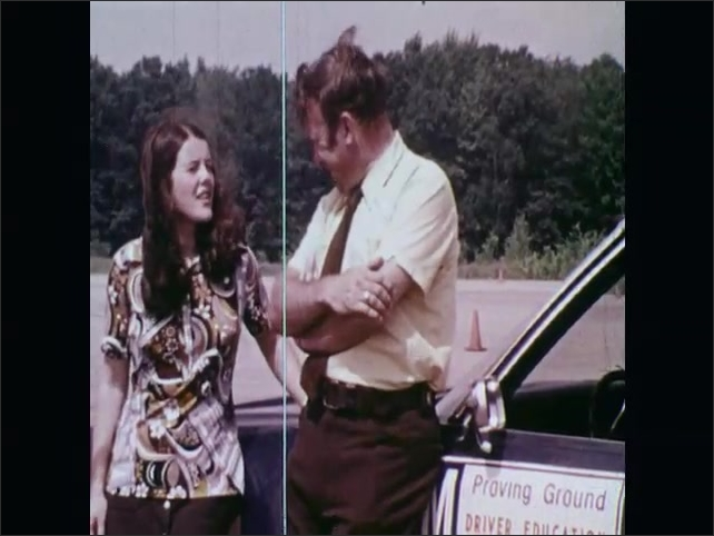 1970s: UNITED STATES: driving student talks to driving instructor. Man talks to girl by car. Driver Education Research.