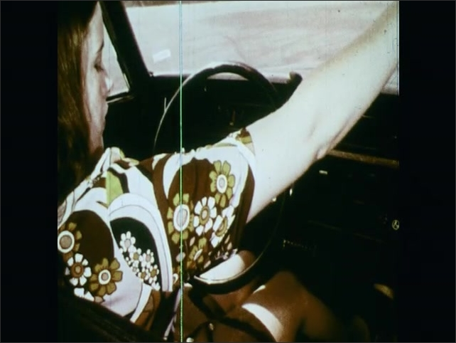 1970s: UNITED STATES: girl sits in car. Girl puts hands on steering wheel. Girl adjusts mirror in car. Girl sits in car during driving lesson.