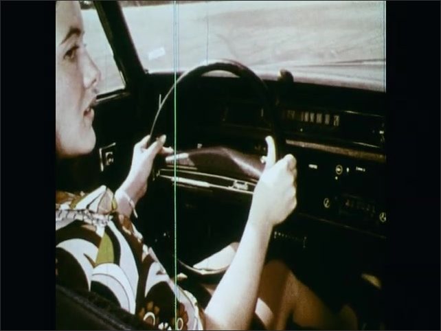 1970s: UNITED STATES: driving instructor talks to student in car. Girl with hands on steering wheel. Girl starts car. Girl puts car into drive.