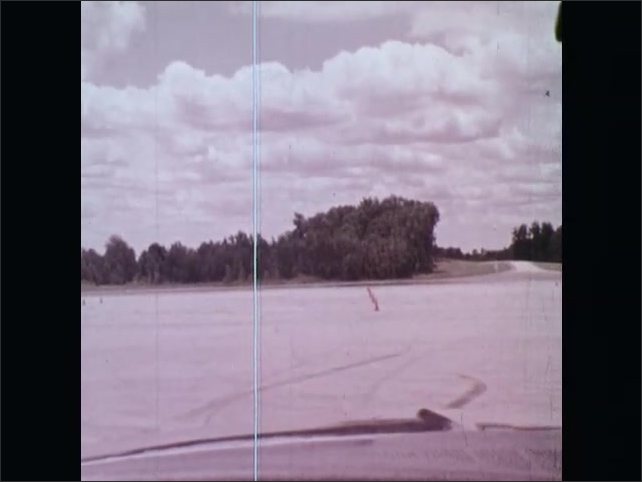 1970s: UNITED STATES: girl sits in driver's seat of car. View of proving ground from car window. Instructor teaches student to drive. Girl starts car.