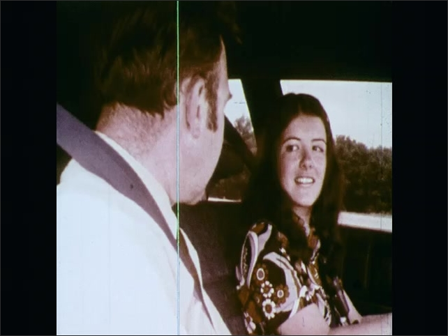 1970s: UNITED STATES: driving instructor talks to girl in car. Girl smiles at instructor. Girl drives slalom through cones.