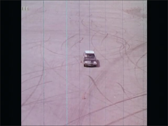 1970s: UNITED STATES: overhead view of car on proving ground. Car drives slalom, Girl in car.
