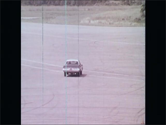 1970s: UNITED STATES: overhead view of car on proving ground. Girl gets lesson with instructor.