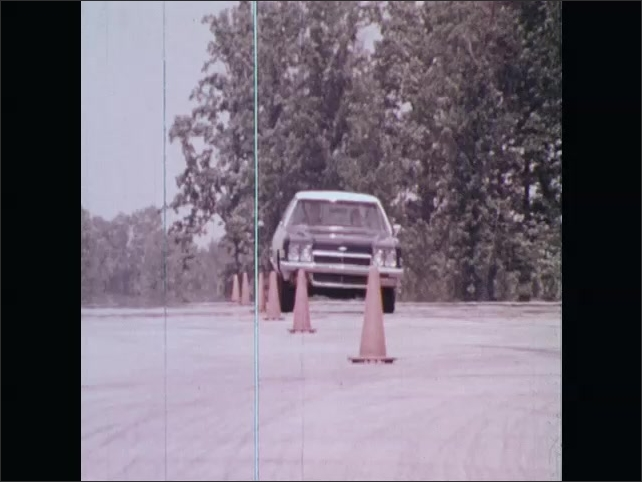 1970s: UNITED STATES: car by traffic cones. Car drives between cones.