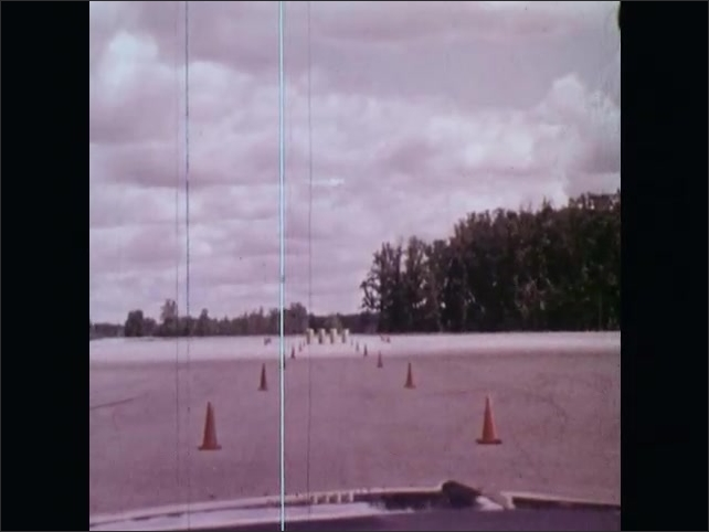 1970s: UNITED STATES: student sits in car during driving lesson. Instructor gives student instructions. Car knocks over cones.