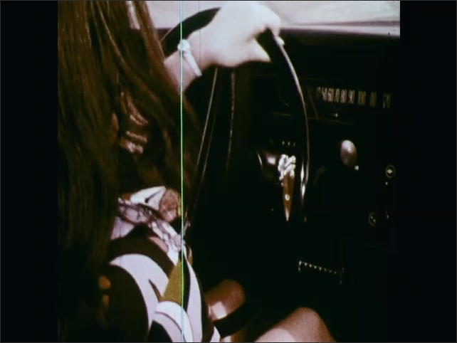 1970s: UNITED STATES: close up of driving instructor's face. Barrels on track. Girl avoids barrels on track.