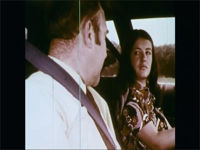 1970s: UNITED STATES: driving instructor talks to student during lesson. Interior of car during lesson. Traffic cones on track. Girl looks at instructor.
