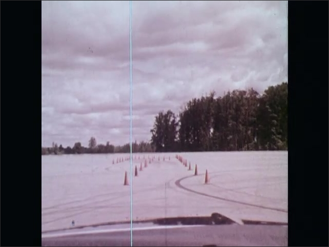 1970s: UNITED STATES: instructor talks to student in car. View of traffic cones on proving ground. Blocked road. Car avoids traffic cones on road.