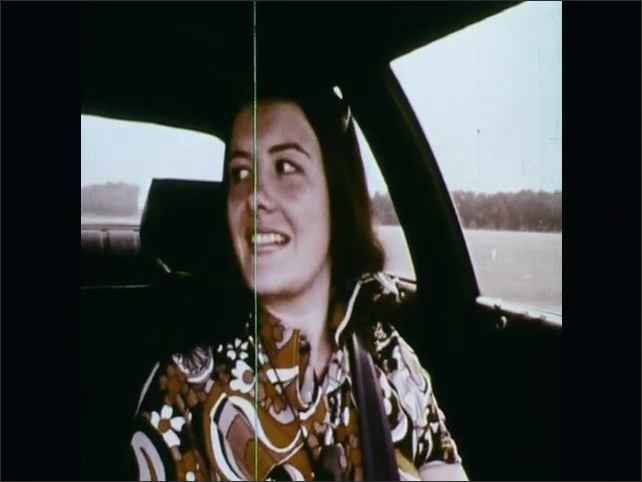 1970s: UNITED STATES: interior view of driving instructor and student in car. Hands pull on steering wheel. Girl drives car. Traffic cones on proving ground