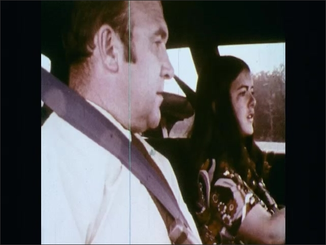 1970s: UNITED STATES: car drives between traffic cones. Front view of car on proving ground. Interior view of student and instructor