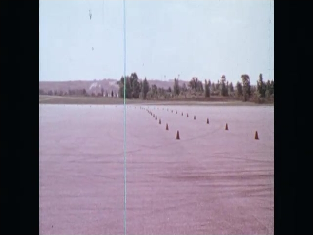 1970s: UNITED STATES: driving instructor smiles at student. Student drives car. View of skid course and traffic cones. Cone marked lane on skid exercise.