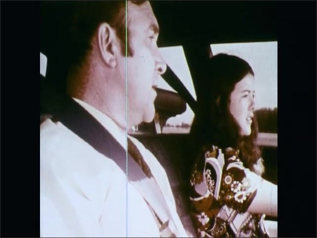 1970s: UNITED STATES: finger hovers over button. Skid lane exercise on proving ground. Girl drives car, Instructor talks to student in car. Girl turns car around