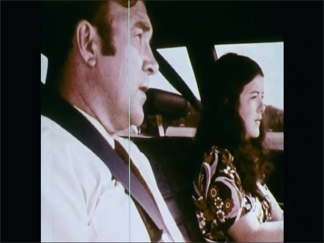 1970s: UNITED STATES: interior view of student and instructor during driving lesson. Overhead view of car on road. Student puts car in gear. Hands on steering wheel. Mirror in interior of car.