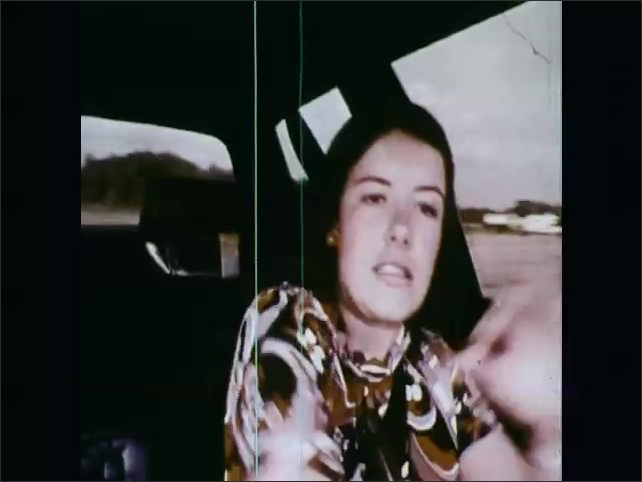 1970s: UNITED STATES: close up of student's face in driving seat. Car skids on water. Student stalls car. Over head view of car. Interior mirror in car.