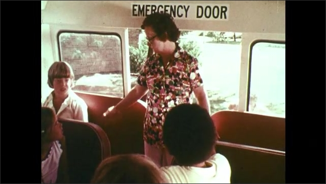 1970s: UNITED STATES: lady stands by emergency door of bus. Lady speaks to students during bus evacuation drill. Students take turns to leave bus.