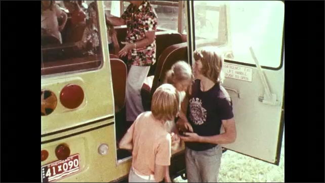 1970s: UNITED STATES: lady helps students leave bus through rear door. Helpers stand by door of bus.
