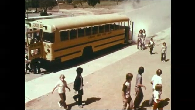 1970s: UNITED STATES: students leave bus through rear door. Diagram of rear and front door evacuation of bus. Driver speaks to students
