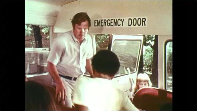 1970s: UNITED STATES: driver walks towards rear door. Students listen to man speak. Driver walks to front of bus