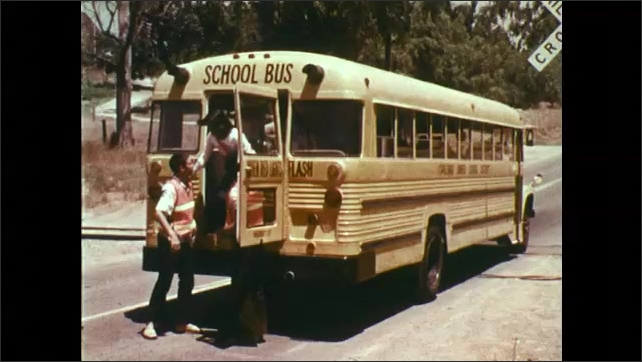 1970s: UNITED STATES: girl jumps from back of bus. Close up of tyre on bus. Students leave school bus during emergency.
