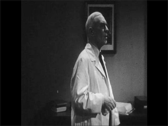 1940s: Doctor dries hands and puts down towel.  Doctor walks to desk.  Young man and doctor speak.