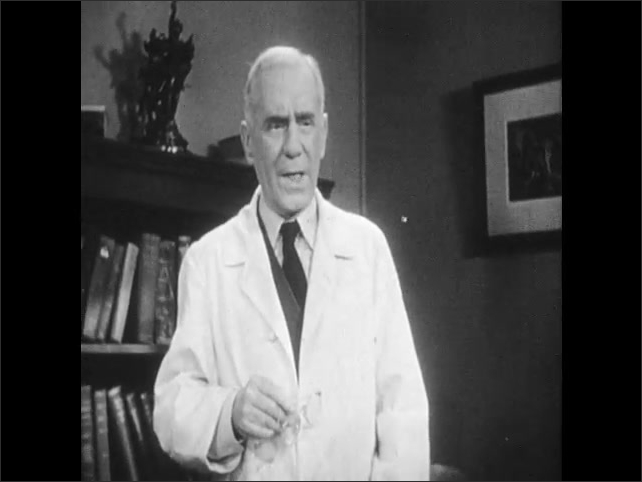 1940s: Office.  Young man and doctor speak.  Doctor stands.