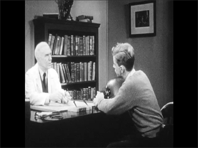 "1940s: Office.  Doctor and young man sit and speak.  Teenage boy paces in front of door marked ""DEAN."""