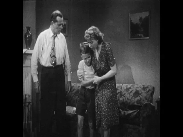 1940s: Girl sits in living room, covers her eyes. Man holding boy by shoulders, shaking him angrily. Woman intervenes, hugging boy and leading him away. Man sits at desk talking.